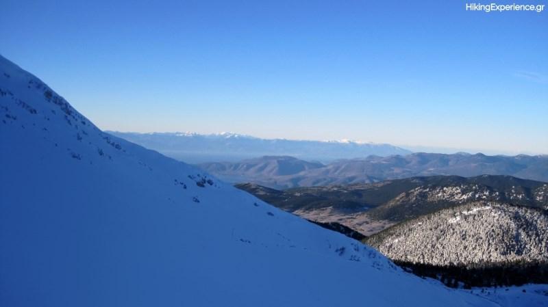 Θέα προς τα νότια. Διακρίνονται τα Καλύβια Λιβαδιού Αράχωβας, ο κόλπος της Ιτέας και στο βάθος οι χιονισμένες Ζήριες και ο Χελμός (δεξιά)